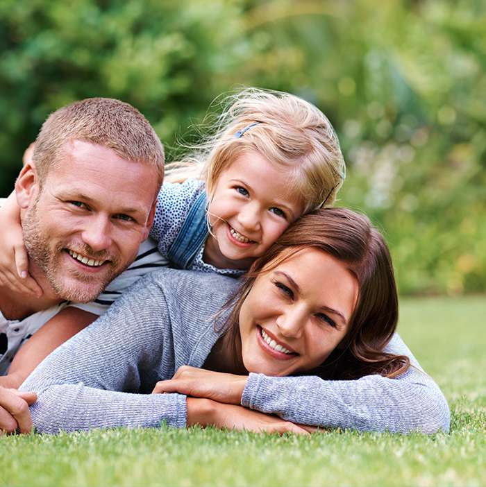 Family of three laying on grass smiling
