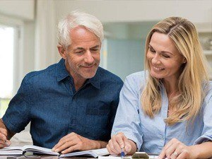 Older man and woman smiling and looking at paperwork