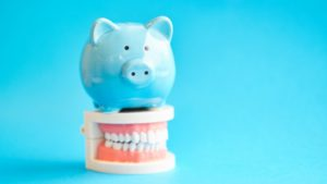 blue piggy bank on top of dentures with blue background