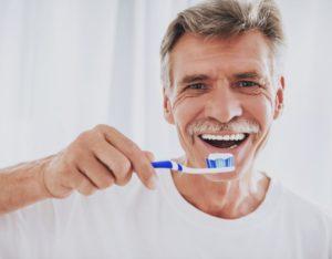 older man brushing his teeth until dentist in Fayetteville reopens