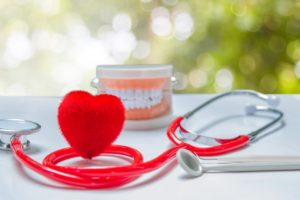 Heart shape and model teeth next to Fayetteville dentist stethoscope
