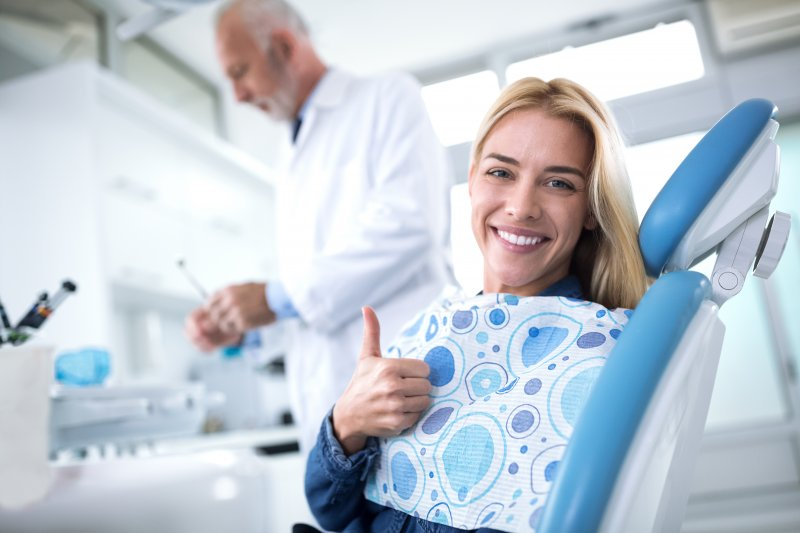 A young female patient giving a thumbs up after seeing her dentist for a checkup