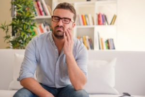 man sitting on couch holding his mouth in pain